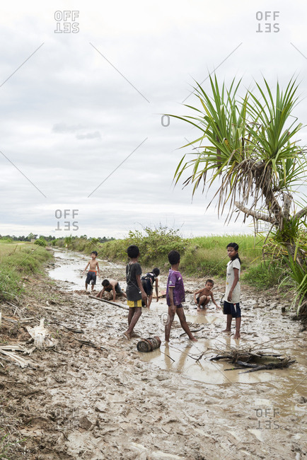 Siem Real, Cambodia - December 4, 2017: Group of kids fishing with hands in a muddy canal barefoot