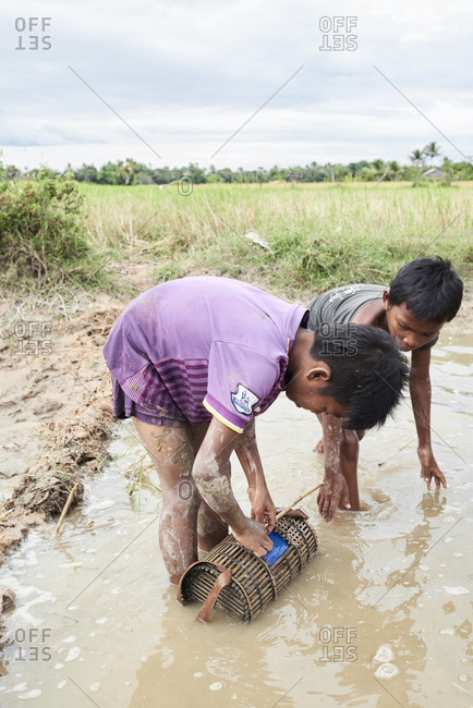 Siem Real, Cambodia - December 4, 2017: Two kids working together catching fish in dirty muddy canal
