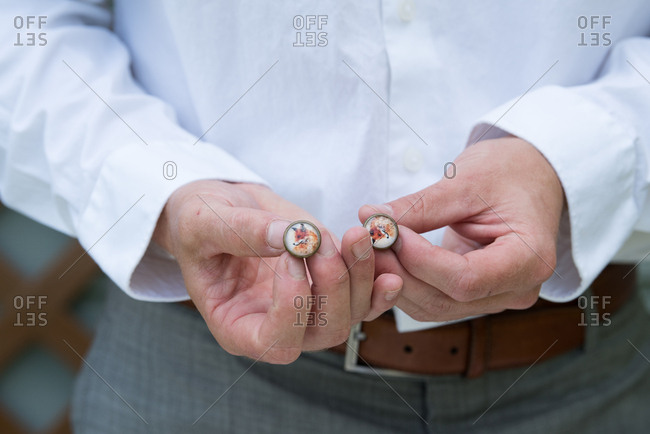 Close-up of groom holding cufflinks