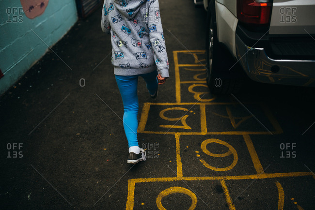 Young girl walking over hopscotch board painted on ground in between parked cars