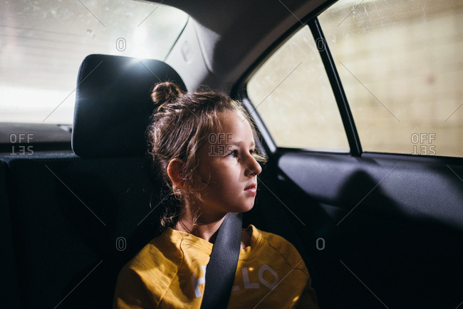 Portrait of young girl looking out car window in tunnel