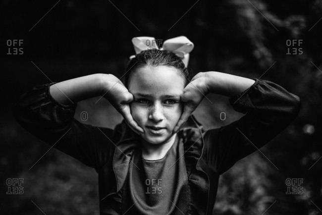 Black and white portrait of young girl dressed for special occasion with hands on face