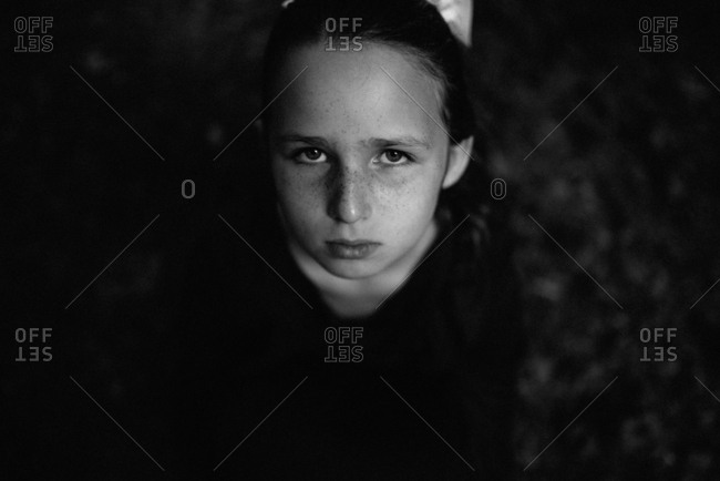 Black and white portrait of unhappy young girl looking up at camera