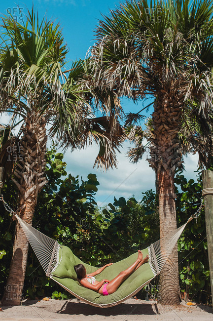Teenage girl lying in hammock hung between two palm trees