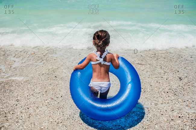 Rearview of little girl with giant rubber ring at water's edge at the beach
