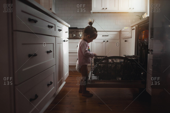 Side view of toddler helping in kitchen loading dishwasher