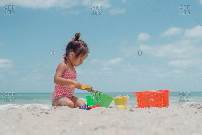 Side view of little girl playing in the sand with bucket and spade at beach