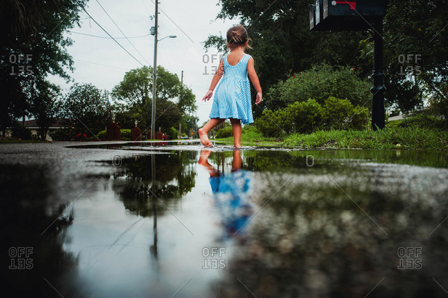 Low angle view of little girl wading in puddle in bare feet