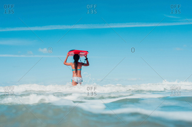 Rearview of young girl carrying boogie board on head wading in ocean at beach