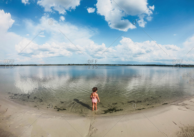 Wide angle view of little girl walking into lake