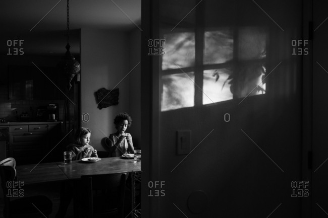 Two girls sitting at dining table talking lit by light from window