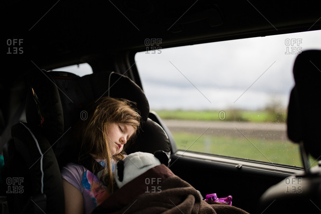 Young girl asleep in back seat of car carrying stuffed animal