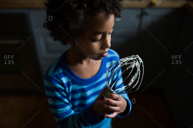high angle view of young girl in kitchen licking whisk covered in cake batter