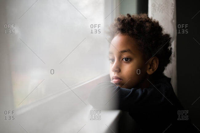 portrait of young girl leaning on window sill looking out window