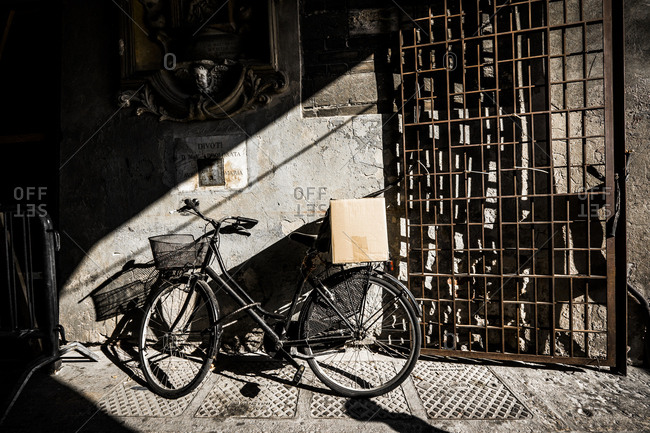 Bicycle parked in an alley with a cardboard box