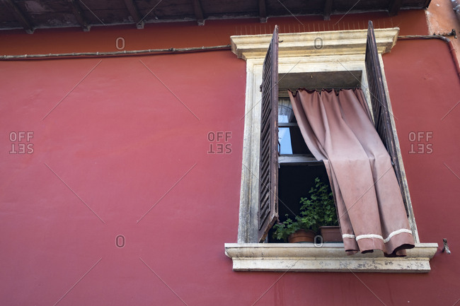 Detail of the window of an Italian house with the curtain on the outside