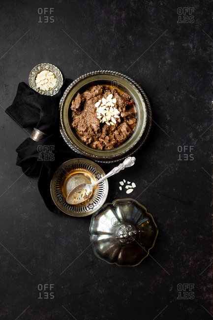 Goat curry prepared with royal spices served on vintage silver props