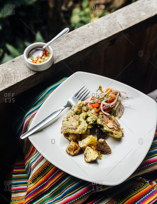 Single serving of chicken and relish on balcony dining table