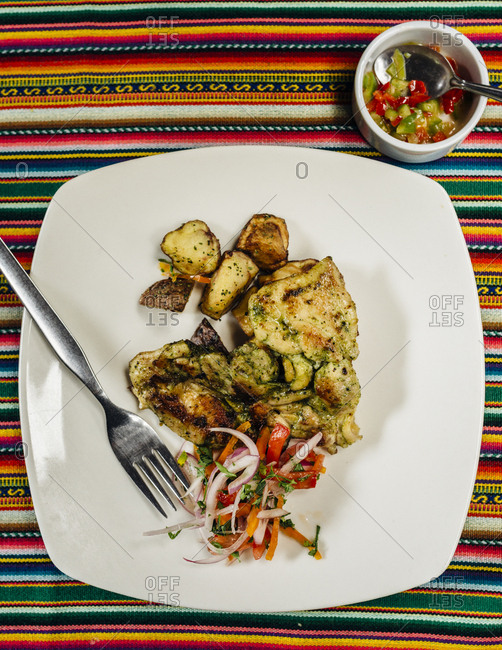 Top view of chicken dish with peppers and onions on striped tablecloth