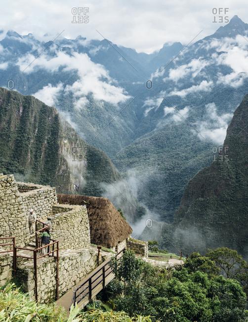 Machu Picchu, Peru - November 20, 2017: Tourism walking up stone steps in Andes mountains