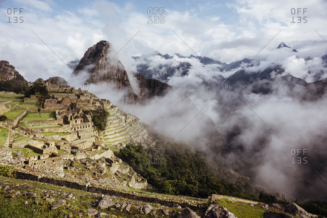 Historic stone village in misty Andes mountain range