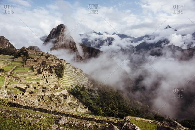 Historic stone village in misty Andes mountain range