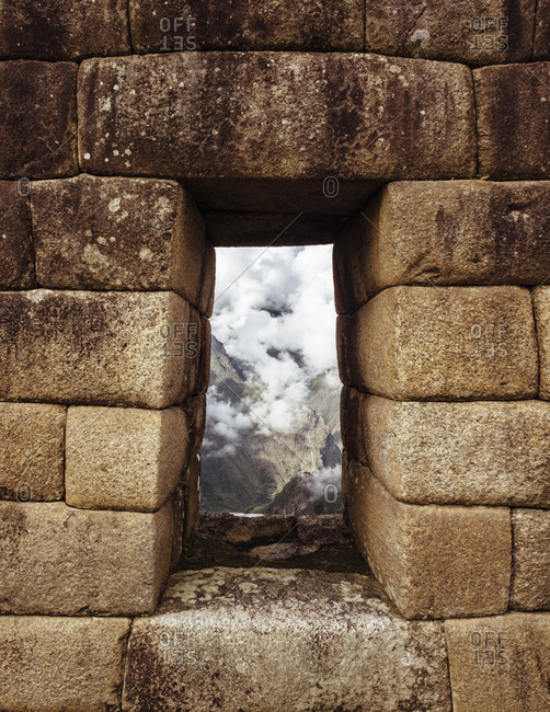 Opening through stone wall in Machu Picchu ruins