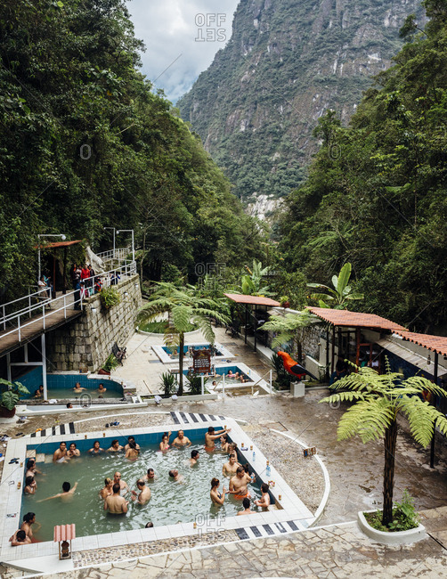 Machu Picchu, Peru - November 20, 2017: Tourists swimming in outdoor pool in Andes mountain range