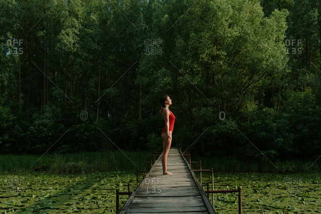 Woman in red bodysuit doing yoga on a narrow wooden bridge on the lake in the woods