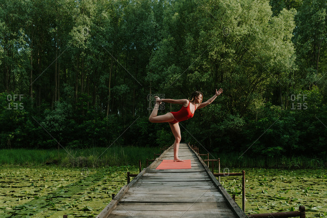 Woman in red bodysuit doing yoga on the narrow wooden bridge on the lake in the woods