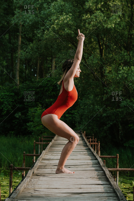 Young woman in red bodysuit doing yoga on a wooden bridge on the lake in the woods