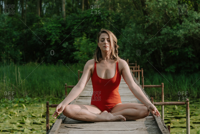 Woman in red bodysuit doing yoga while sitting on a wooden bridge on the lake in the woods