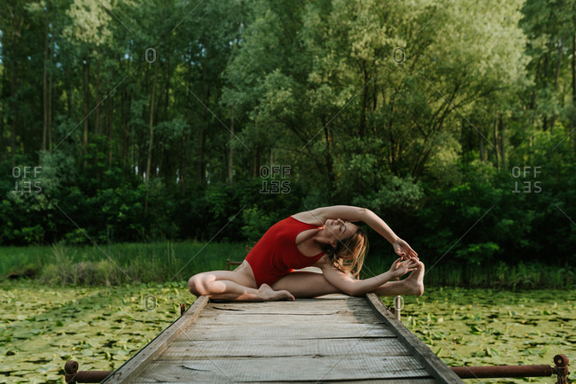 Woman in red bodysuit stretching on the narrow wooden bridge on the lake in the woods