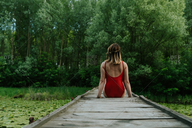 Woman sitting on a wooden bridge in the woods wearing red bodysuit looking relaxed