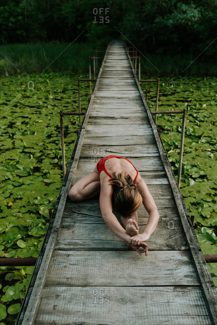 Elevated view of woman in red bodysuit doing yoga on a narrow wooden bridge on the lake