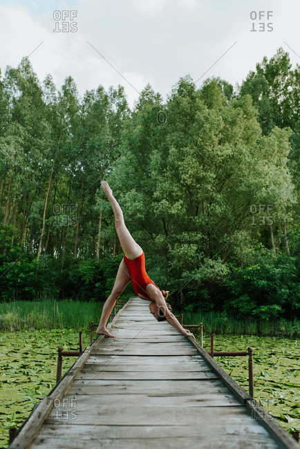 Woman in red bodysuit doing yoga on the lake in the woods