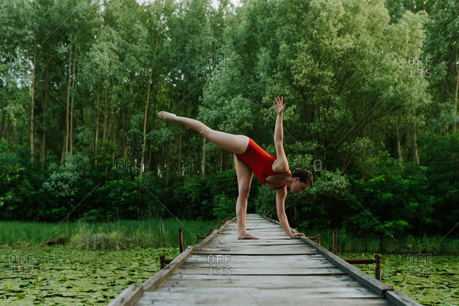 Woman in red bodysuit doing yoga poses on the lake in the woods