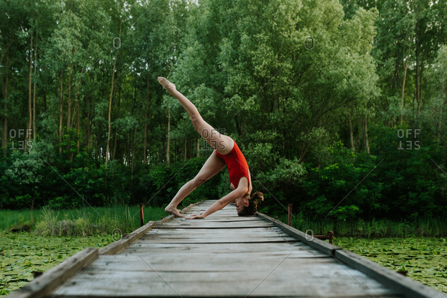 Woman in red bodysuit doing yoga poses on a lake in the woods