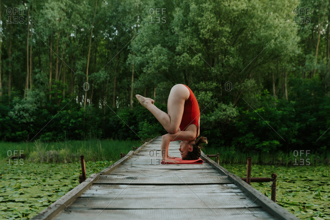 Woman in red bodysuit doing yoga poses on a lake in the forest
