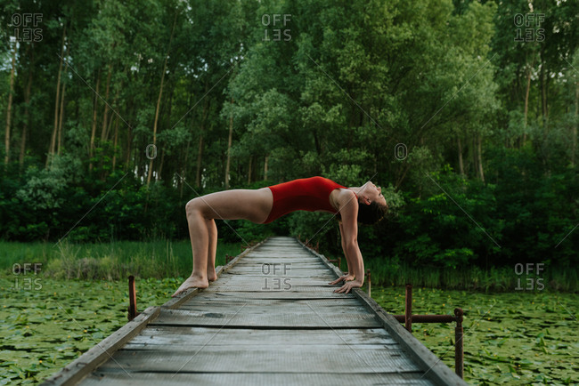 Young woman in red bodysuit doing yoga poses on a lake in the forest