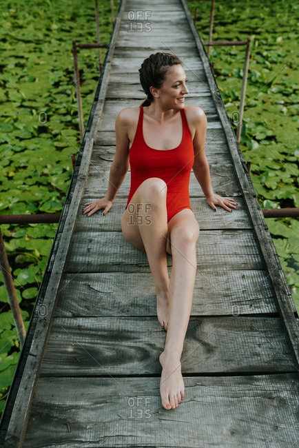 Woman in a red bodysuit doing yoga on the narrow wooden bridge on the lake in the woods