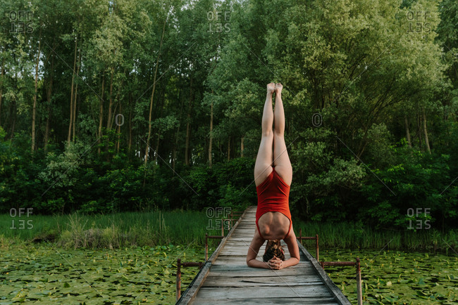 Woman in red bodysuit doing a headstand on a wooden bridge on the lake in the woods