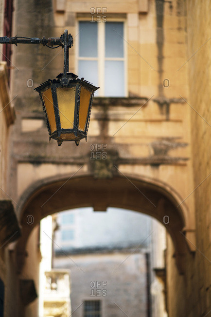 Low angle view of antique hanging lantern in sunny alley
