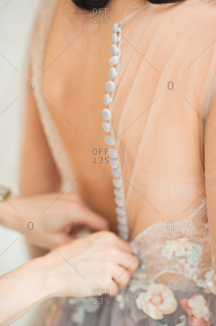 Woman buttoning up back of bride's gown