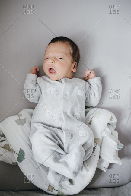 Infant boy yawning on his back with blanket