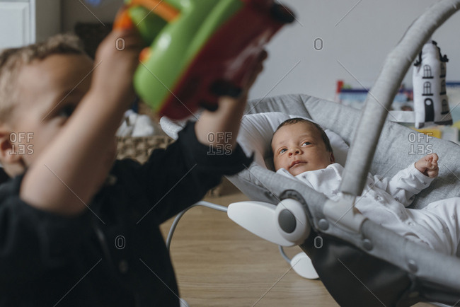 Newborn watching older brother playing with toy