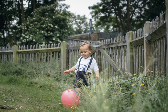 Little boy kicking rubber ball in the yard