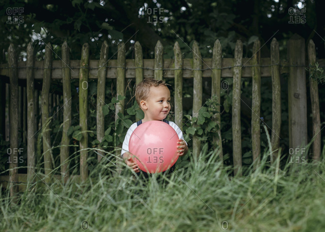 Shy toddler holding rubber ball against wooden fence