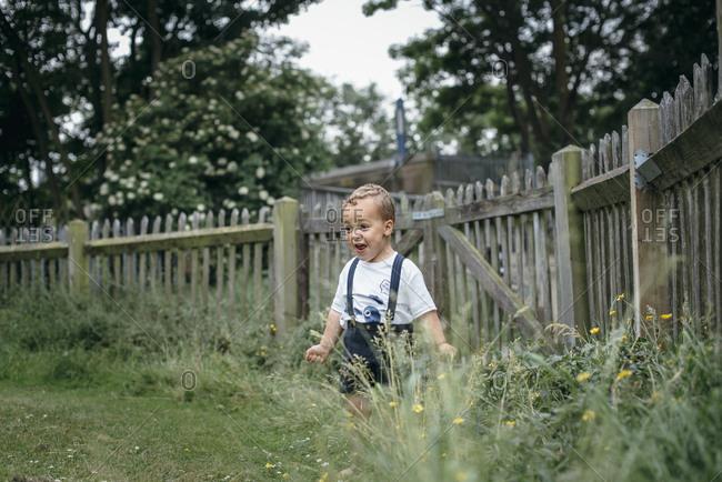 Excited toddler boy shouting in corner of garden