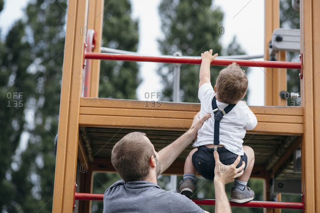 Father helps his son climb up playground equipment